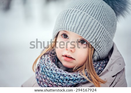 cute smiling baby girl winter portrait in warm knitted hat and scarf  - stock photo
