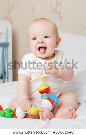 Cute smiling baby laughing and smiling with a toy in his hand. Laugh, smile, good humor, toy. - stock photo