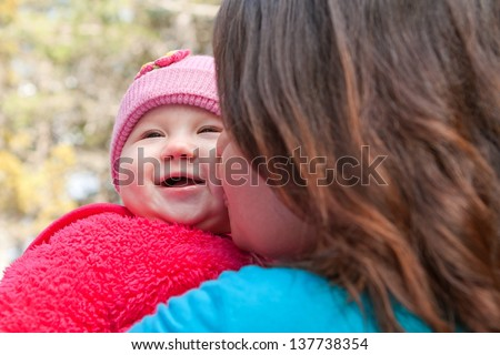 Cute smiling baby receiving a kiss from her mom - stock photo