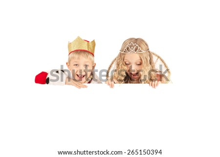 Cute smiling boy and girl in the king and queen costumes holding the sign - stock photo