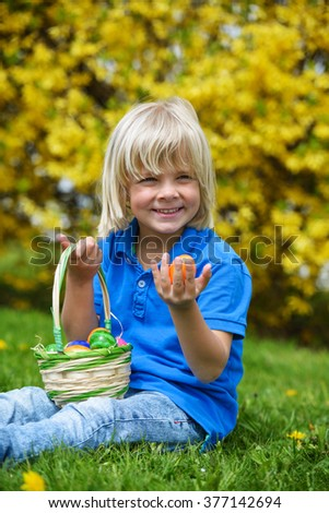 Cute  smiling boy holds colored easter eggs outdoors on a sunny day - stock photo
