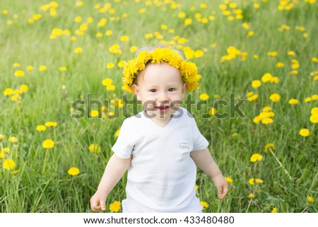 Cute smiling boy in dandelion wreath in the spring field