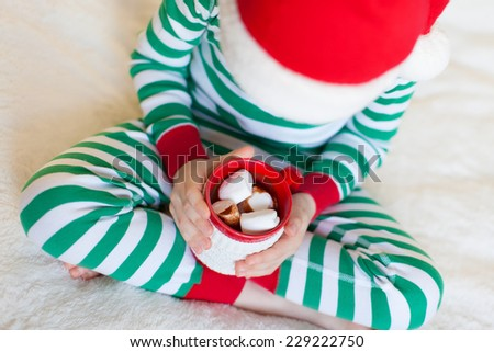 cute smiling boy sitting cozy at home, holding cup of hot cocoa at christmas time - stock photo