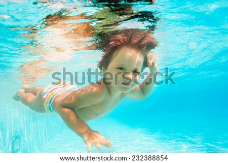 Cute smiling boy swimming under water of pool - stock photo