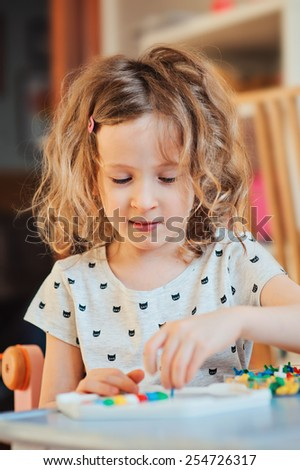 cute smiling child girl playing at home with colorful mosaic
