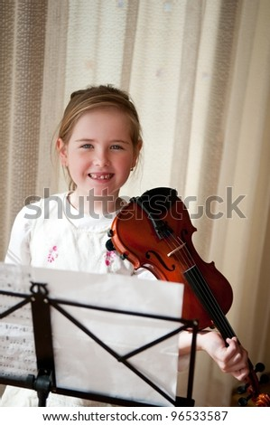 Cute smiling child (little girl) holding violin indoors - stock photo