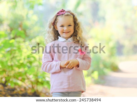 Cute smiling child outdoors in warm sunny day - stock photo