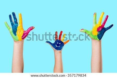 Cute smiling colorful painted hand on blue background.