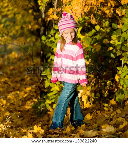 Cute smiling girl against autumn leaves