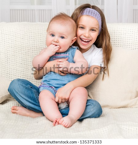 cute smiling girl and her little sister at home