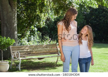 Cute smiling girl and mother standing in the park