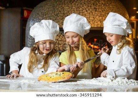 cute smiling girl chef admiring look at pizza - stock photo