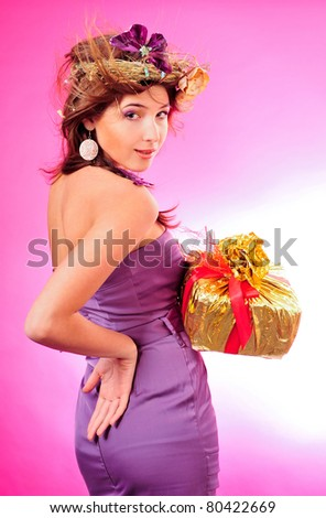 Cute smiling girl holding the golden box with red tape present over pink background