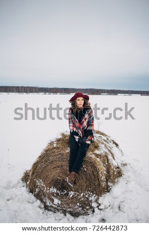 Cute smiling girl in a hat near the snow-covered stacks in winter. Toning