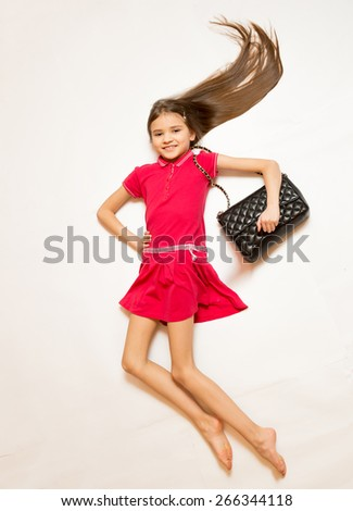 Cute smiling girl in red dress and handbag posing on floor - stock photo