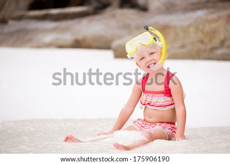 Cute smiling girl on the white beach wearing mask and snorkel - stock photo