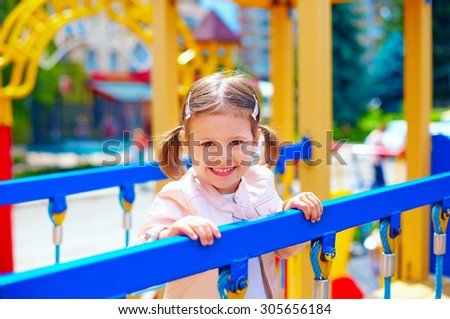 cute smiling girl playing in preschool, on playground - stock photo