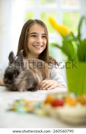 Cute smiling girl siting  for the Easter table with bunny - stock photo