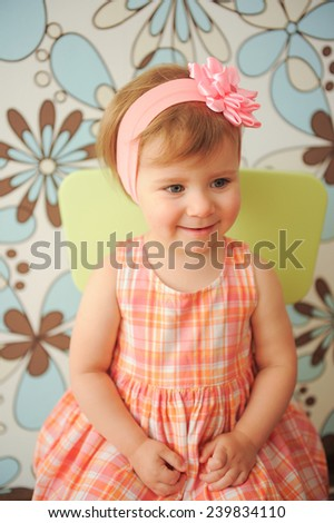 cute smiling girl sitting on chair - stock photo