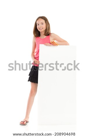 Cute smiling girl standing behind blank banner. Full length studio shot isolated on white. - stock photo