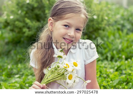 Cute smiling girl with a bouquet of daisies on green background