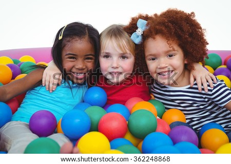 Cute smiling girls in sponge ball pool hugging and looking at the camera - stock photo