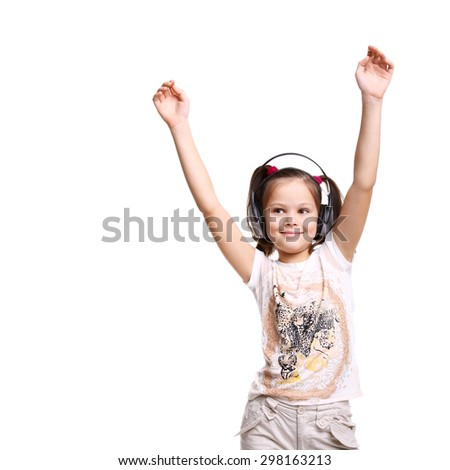 cute smiling happy little child in the headphones with her hands up