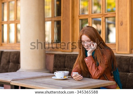 Cute smiling happy young female with beautiful long red hair in leather jacket drinking coffee and using smartphone in outdoor cafe - stock photo