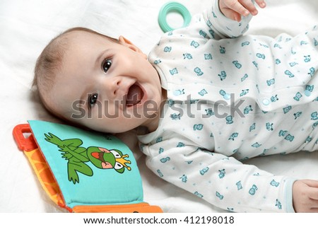 Cute smiling infant lying in his bed with different toys - stock photo