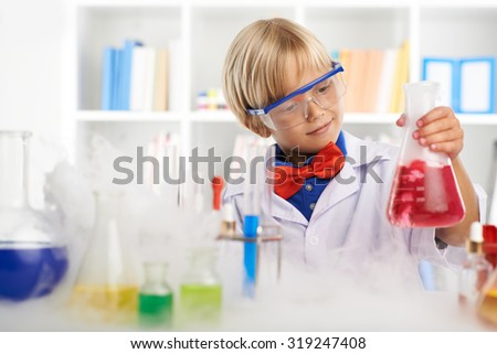 Cute smiling kid looking at the flask with red liquid