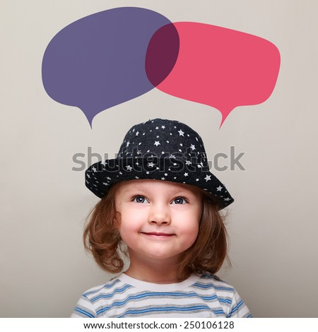 Cute smiling kid looking up on two colorful balloons above on grey background - stock photo