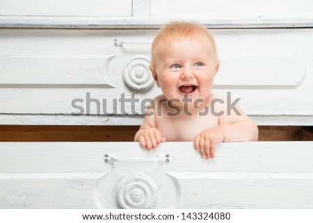 Cute smiling little baby in a drawer - stock photo
