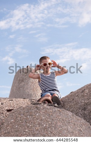 Cute smiling little boy in sunglasses and a vest sitting on a concrete breakwater on blue sky background