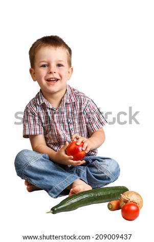 Cute smiling little boy with healthy vegetables and fruits from the garden