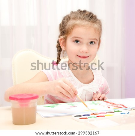 Cute smiling little girl drawing with paint and paintbrush at home