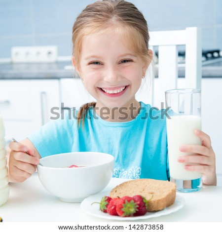 cute smiling little girl drinking milk in the kitchen - stock photo