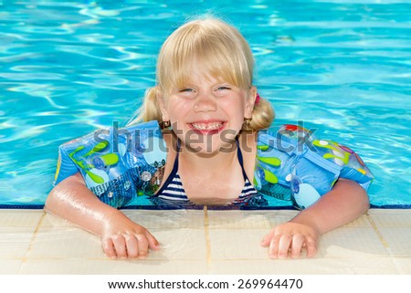 Cute smiling little girl hold ball in the swimming pool