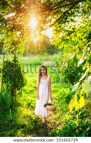 Cute smiling little girl holds basket  with fruit and vegetables at the farm. Portrait of adorable small kid outdoor. - stock photo