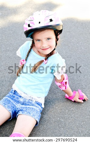 Cute smiling little girl in pink roller skates and protective gear outdoor - stock photo