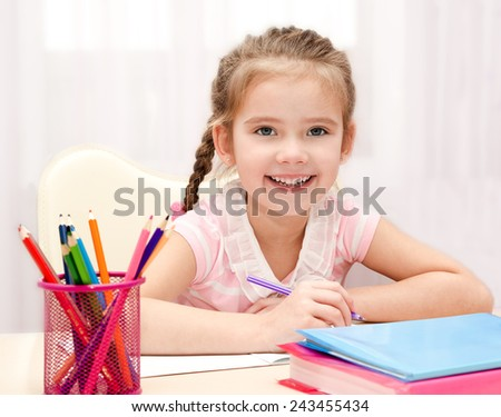 Cute smiling little girl is writing at the desk at home - stock photo