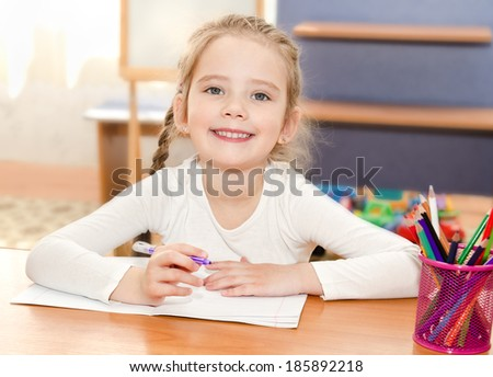 Cute smiling little girl is writing at the desk  in preschool - stock photo