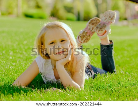 Cute smiling little girl lying on grass in the park