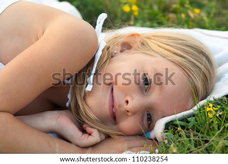 Cute smiling little girl lying on the blanket on the meadow on beautiful summer day. - stock photo