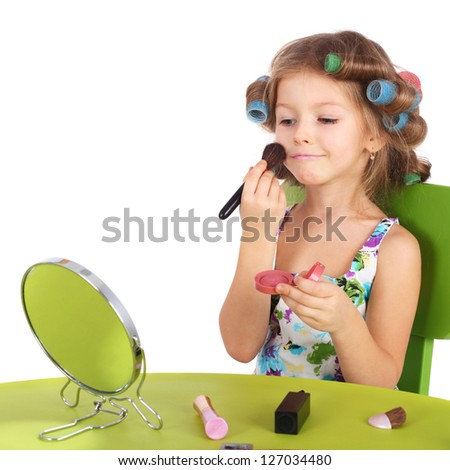 cute smiling little girl making makeup