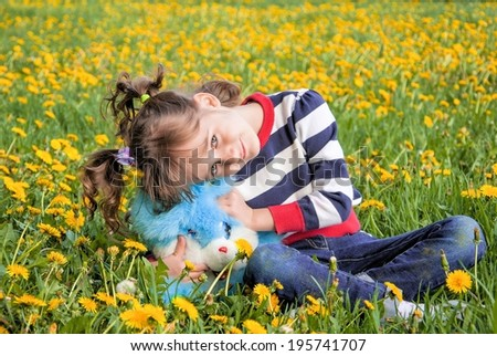 Cute smiling little girl on a background of yellow dandelions and green lawn