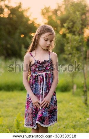 Cute smiling little girl on the meadow at the farm. Portrait of adorable small kid outdoor. Sunset. - stock photo