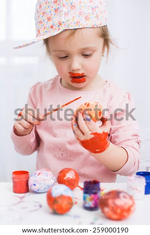 Cute smiling little girl painting colorful easter eggs - stock photo