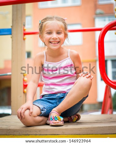 cute smiling little girl play on a playground - stock photo
