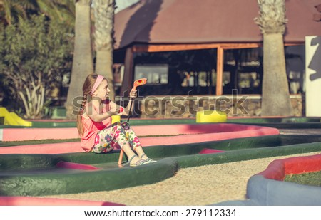 Cute smiling little girl playing golf - stock photo