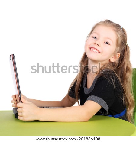 cute smiling little girl playing with computer - stock photo